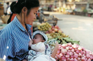 A mother breastfeeds as she tends her produce market stall.