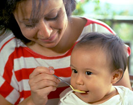 A mother feeds her baby complementary food with a spoon as he sits on her lap.